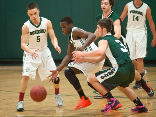 Winooski's Eddie Lamson, center, steals the ball from Enosburg's Brandyn Robtoy, right, during the second half of Saturday's boys basketball game.