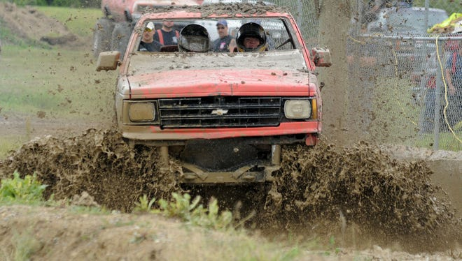 James Devroy drives his truck though the pit on his first run during the mud bog races in 2013 at the Yale Lions Club.  TIMES HERALD