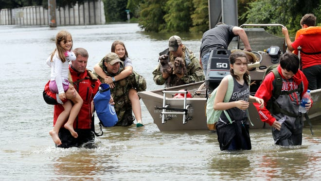Residents are rescued from their homes surrounded by floodwaters from Tropical Storm Harvey on Aug. 27, 2017, in Houston, Texas.