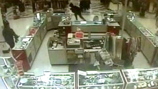 Surveillance video shows an Air Force officer and a robbery suspect grappling in a TJ Maxx in Evesham in January 2014.