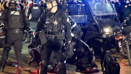 Police attend to a wounded man during a protest at the University of Washington on Friday night.
