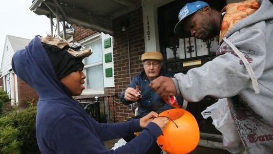 Zanaija McIntrye of Detroit goes trick or treating on Alma St. in Detroit and gets candy from Nick DiNunzio and Charles Fuqua on Halloween last year.