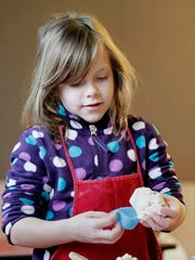 Ella Biemann, 7, of Milwaukee, creates a muffin out
