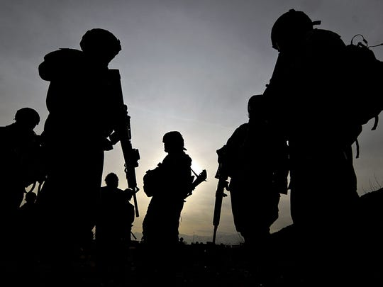 U.S. soldiers with the NATO-led International Security Assistance Force (ISAF) silhouetted as they walk during a patrol outside Bagram Airbase, some 50 km north of Kabul.