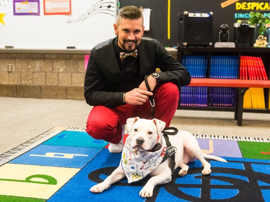 """Cole the Deaf Dog, pictured with his """"dad"""" Chris Hannah,  Mennies Elementary School music teacher. File photo"""