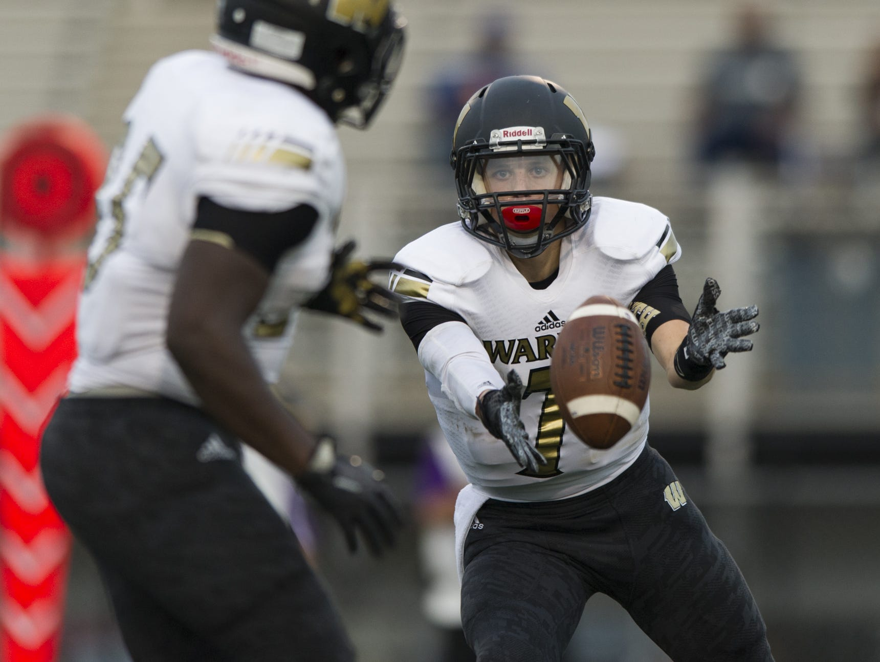 Warren Central High School junior quarterback Zach Summeier (7) pitches the ball to teammate senior Terry Hart (35) in the backfield during first-half action of a IHSAA varsity football game at Ben Davis High School, Friday, September 18, 2015.