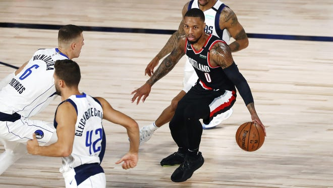 Portland's Damian Lillard dribbles while defended by Dallas forward Kristaps Porzingis (6) Tuesday, Aug. 11, 2020, in Lake Buena Vista, Fla.