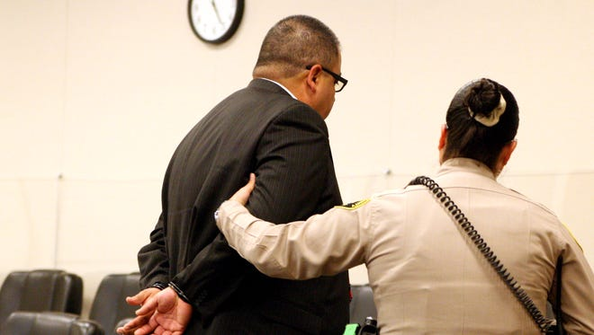 A sheriff's deputy leads away Bobby Carrillo in handcuffs on Friday.
