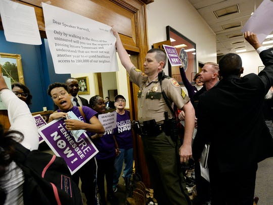 Tennessee state troopers remove signs taped to the entrance of House Speaker Beth Harwell's office at Legislative Plaza on Tuesday, April 5, 2016, in Nashville. The protesters brought or mailed old shoes to Harwell's office with stories of working poor residents who need insurance but cannot get it.