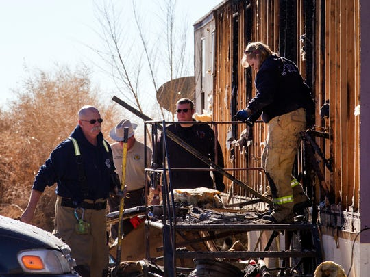 Members of the San Juan County Fire and Explosion Task Force search for clues Thursday at the scene of a Wednesday night house fire  in Kirtland that killed two young children.