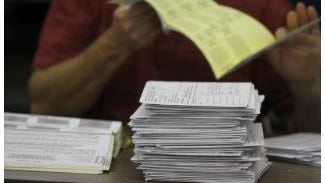 Mail ballots are counted at the Rhode Island Board of Elections in 2014.