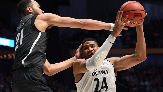 Cincinnati forward Kyle Washington rebounds against Nevada guard Kendall Stephens during their NCAA Tournament game Sunday in Nashville, Tenn.