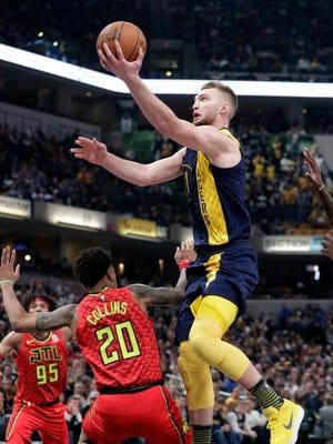 Indiana Pacers center Domantas Sabonis (11) shoots over Atlanta Hawks forward John Collins (20) during the first half of an NBA basketball game in Indianapolis, Friday, Feb. 23, 2018. (AP Photo/Michael Conroy)