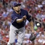 Milwaukee Brewers starting pitcher Matt Garza tosses the ball to first base in an attempt to force out St. Louis Cardinals' Matt Adams during the fourth inning of a baseball game Friday, July 1, 2016, in St. Louis. Garza tossed the ball wide allowing Adams to reach base on the throwing error.