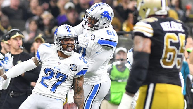 The Lions' Glover Quin celebrates with Kerry Hyder after Quin's interception in the third quarter.