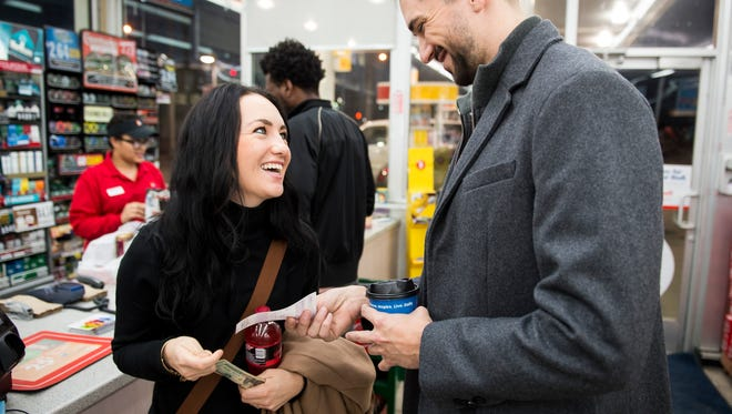 Laura Bolter, left, and Christian Grabeman, right, laugh after they bought five lottery tickets at a Daily's Convenience Store Friday, Jan. 8, 2016, in Nashville, Tenn. The current jackpot is $800 million.