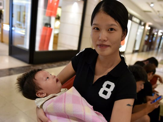 "Angelina Chen, 24, enjoys some air conditioning with her 3-month-old son, Carlos Li, at T-Galleria in Garapan on Aug. 11. Chen's roof and two walls blew away during the storm. She and her husband huddled on the floor and held on tight, protecting baby Carlos between their bodies. ""We cannot go outside, there is nowhere to go. So we stayed and held baby together,"" said Chen."