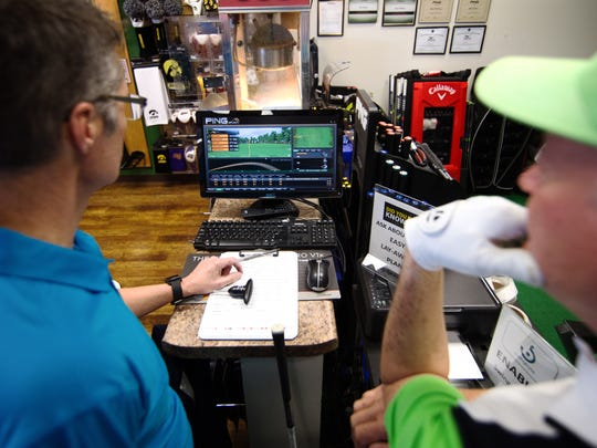 Owner Bruce Brooke helps fit Jon Styre with swing-specific data on a Swingbyte-enabled machine at GolfUSA of Coralville.