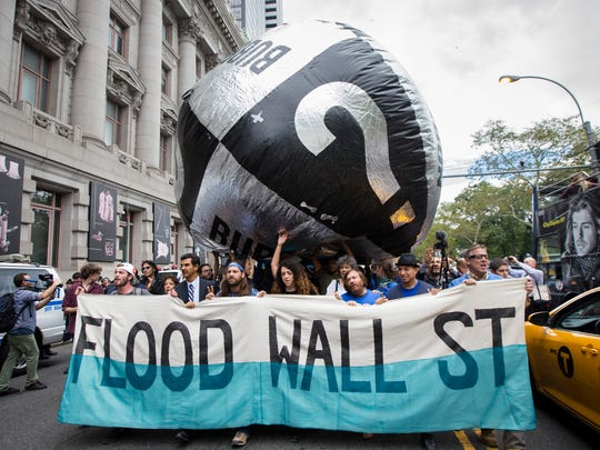 Demonstrators march towards Wall Street from Battery Park to protest for action on climate change and corporate greed on Monday, a day after a huge climate march in New York City.