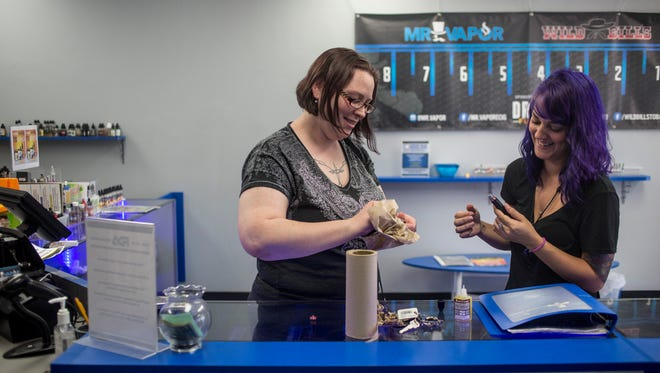 Customers Cybelle Arana, of Texas, right, helps Crystal Navoni, of Port Huron, with repairing her vaporizer after an employee had to refuse to offer help due to new FDA regulations that bar them from handling a customers device Friday, August 12, 2016 at Mr. Vapor in Port Huron. Navoni began using a vaporizer to help her quit smoking cigarettes.