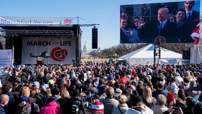 President Donald Trump speaks via a live feed to anti-abortion activists as they rally on the National Mall in Washington, Jan. 19, 2018, during the annual March for Life. Thousands of anti-abortion demonstrators gather in Washington for an annual march to protest the Supreme Court's landmark 1973 decision that declared a constitutional right to abortion.