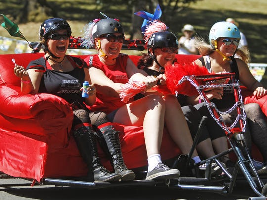 "The Cherry City Derby Girls team, ""Cruisin for a Bruisin"" speeds down the hill at the 2nd Annual Capitol City Couch Race at Bush's Pasture Park Saturday Aug. 4, 2012."
