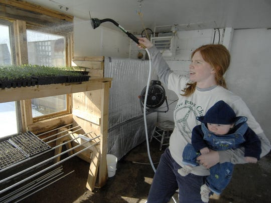 Kat Becker holds 10 week old Riley Schultz-Becker as she waters organic plants in one of the greenhouses at Stoney Acres Farm in rural Athens in 2008.