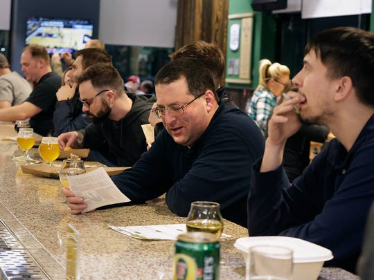 Jamie Ogas (from left) and Scott Dobert figure out an answer while enjoying the atmosphere during Trivia Night at the Tosa Tavern, a bar in the Whole Foods store, Wauwatosa. Large crowds enjoy food, drinks and  playing trivia.