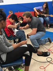 Rick Hansen and Rachael Wilson work with kids during a MAMA music education workshop at the Chisholm Boys & Girls Club.