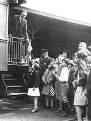 In 1924, President Calvin Coolidge receives a small American flag from 8-year-old Lorraine B. Dinnick of White River Junction.