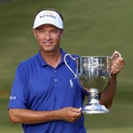Davis Love III poses with the trophy after winning the Wyndham Championship golf tournament at Sedgefield Country Club in Greensboro, N.C. on Sunday.