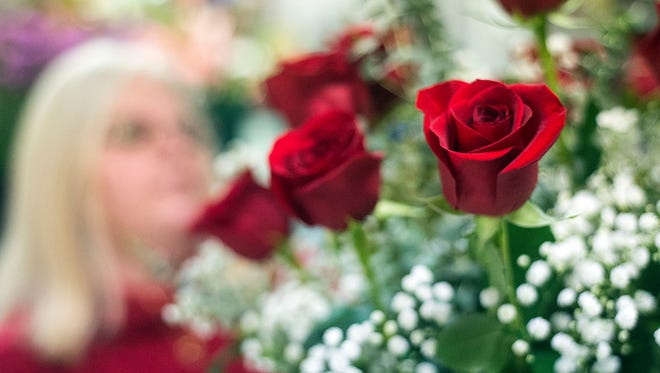 Karen McDermitt eyes the finished arrangement of roses after adding the finishing touches, February 12, 2017. Pressell's usually gets ready for big holidays six months in advance, ordering flowers and brining in designers to arrange the selections.