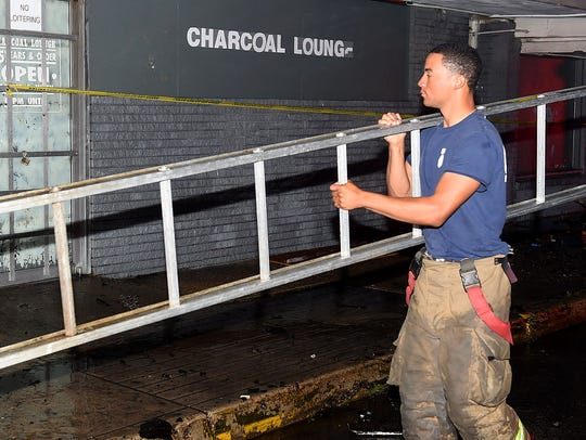 A firefighter from the Opelousas Fire Department removes a ladder from the front of the Charcoal Lounge after an arson fire destroyed the historic establishment. Plans are underway to build apartments where the lounge once stood.