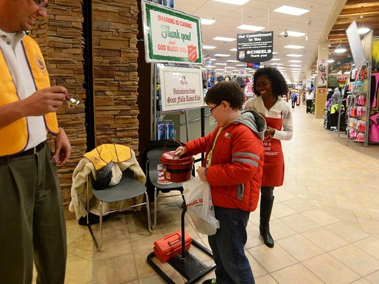 Great Falls Lions Club members Keith Schnider and Raymonde Page receive a donation from Cooper Leiby, age 9, as they volunteer as Salvation Army bell ringers at Scheels in the Holiday Village Mall.