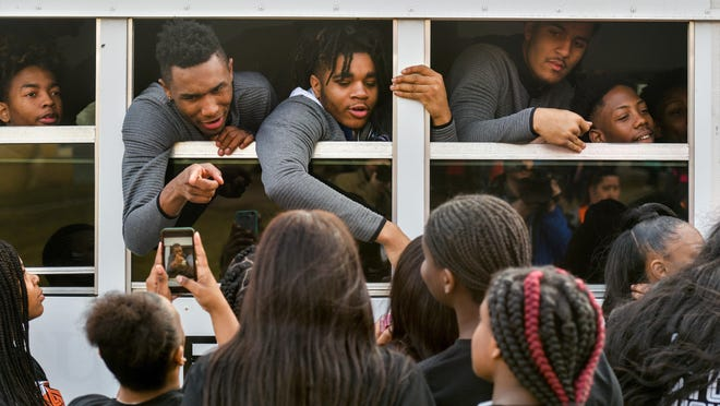 Members of the Manual boys basketball team gathers in the windows of their bus to talk to their cheerleaders before heading to the 2019 Class 3A state finals in Peoria.