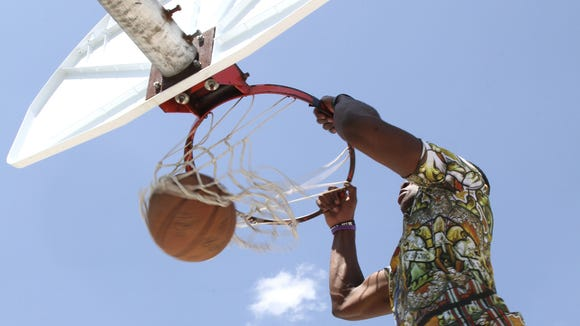 Jacorion Andrews dunks the ball Monday at Saul Adler Community Center's outdoor court.