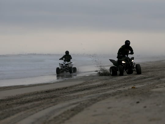 In this June 22, 2016 picture, Border Patrol agents ride all-terrain vehicles along a beach leading to the border with Mexico in San Diego.