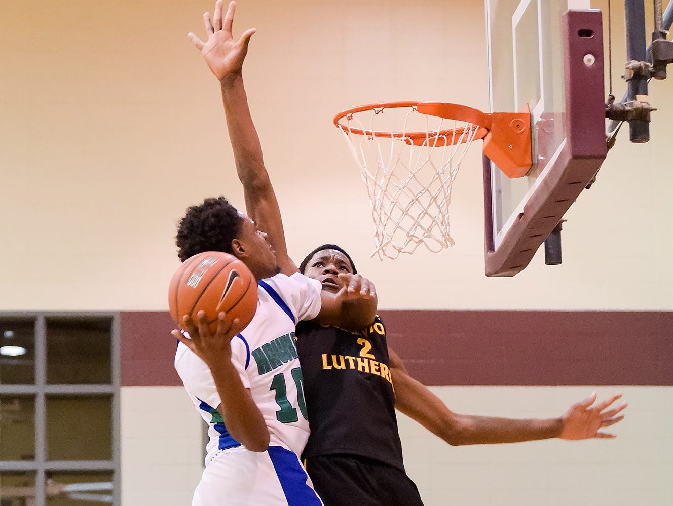 Lamar Hamrick (No. 10) of St. Georges Technical High School takes the ball to the net.
