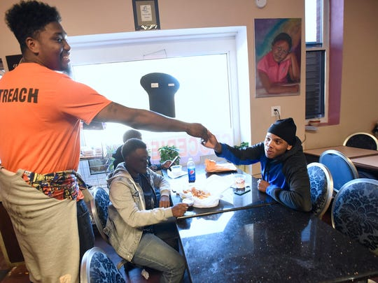 """Paul Frazier, left, of the Baltimore health department's Safe Streets program, greets Tavaz Myles, 19, of Baltimore. Safe Streets cuts gun violence in neighborhoods with help from ex-offenders who are known and respected in the streets. """"Who better to know the streets than the people who grew up on them?"""" one resident said. """"You give them a purpose, and a way to give back.""""  Similar programs operate in New York, Philadelphia, Chicago and New Orleans."""
