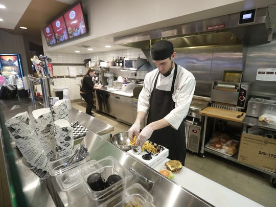 Steven Uphold assembles a burger and fries basket at Marcus Valley Grand Cinema in Buchanan. The restaurant inside the theater is now part of the movie-going experience.