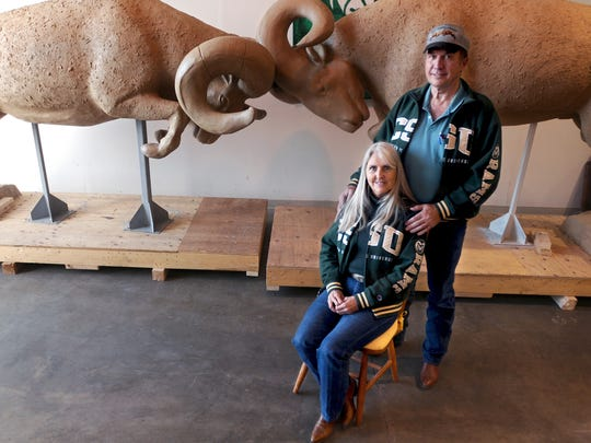 """Sculptor Dawn Weimer is pictured with her husband, Tom, in front of the clay sculpture """"Rocky Mountain Rumble"""" at their studio in Loveland."""