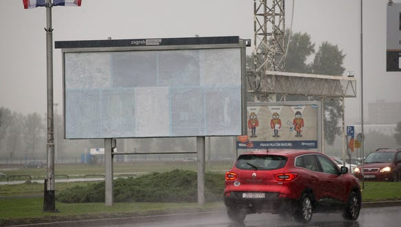 Cars drive past the empty advertising space from which