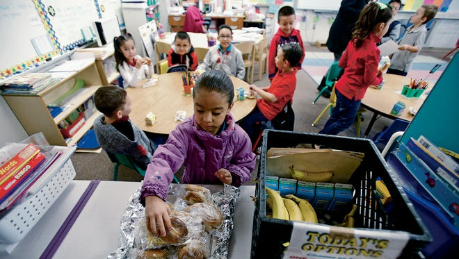 Jayleen Hernandez, 6, gets a bagel for breakfast in her first-grade classroom at Ramirez Thomas Elementary in Santa Fe on Wednesday, Feb. 10, 2016. The Breakfast After the Bell Act passed Legislatively, requiring high-poverty schools to serve breakfast after the start of the instructional day. Original language applied only to elementary schools, and was expanded to middle and high schools in 2014. The law was further tweaked in 2016 to allow schools more flexibility.