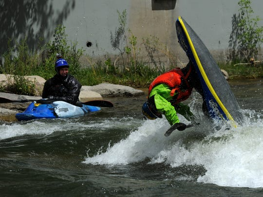Reno's Scott Sady, left, watches fellow boater Stephen Wright play on a wave at the Truckee River Whitewater Park in downtown Reno on April 25, 2016.