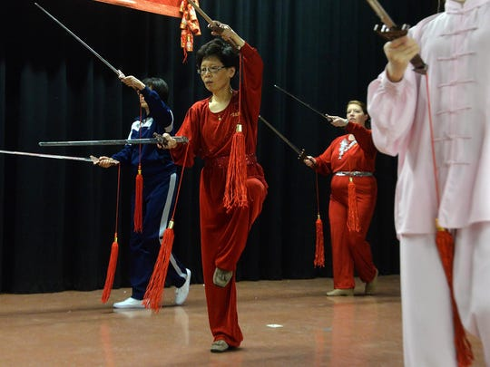 Way Zhang of Marlton (center), a member of the Chinese School of South Jersey's Mulan Boxing class, displays a double sword form in Cherry Hill.