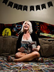 Britney Hawes, 25, of Boise, Idaho, withs with her comic books at her home West Des Moines. Hawes and her husband collect comics together and have amassed a collection that numbers in the thousands.