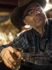 "Gary Bischoff, a lifetime resident of Alzada, enjoys a drink in the Saloon. As a cattle rancher just over the border in South Dakota, he has a hard time finding help. ""It used to be you could ask employees what they could offer you. Now it's what can you offer me? A job, that's what."""