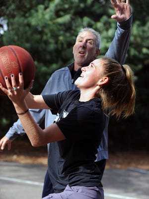 Babson-bound Millis High senior Abby Miller plays one on one with her father, Babson alumnus Matthew, on their backyard basketball court Tuesday afternoon.