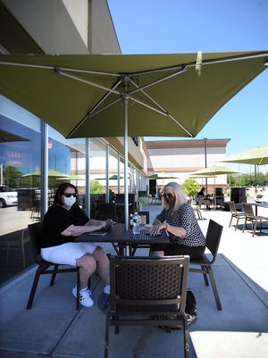 Sisters Carolyn Webb, left, of Milford, and Joanne Murphy, of Mendon, enjoy the shade of an umbrella outside Panera Bread in Milford last week.