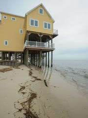 Water approaches the supports of a home on Broadkill Beach on March 25. An estimated 1.9 million cubic yards of sand will be pushed into the water offshore, extending the beach 50 yards into Delaware Bay.